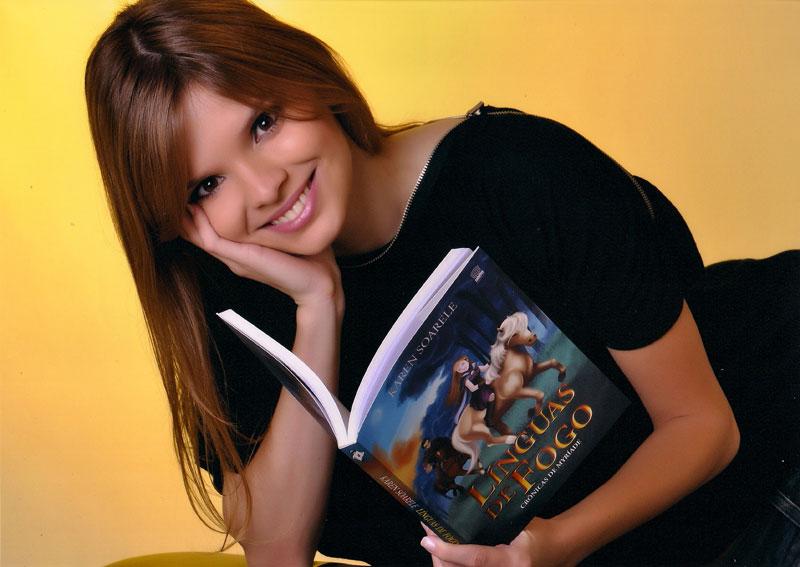 Autora Karen Soarele segura seu livro de estreia, Línguas de Fogo.